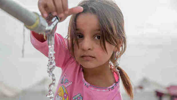 "On 15 November, a young girl from Mosul takes water from a tap stand at a UNICEF-supported Temporary Learning Space in Hassan Sham Displacement Camp, Ninewa Governorate. ""I like it here because we've been out of school for two years,"" she said. Photo: UNICEF"
