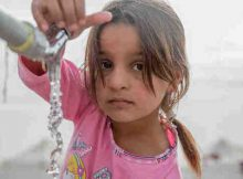 """On 15 November, a young girl from Mosul takes water from a tap stand at a UNICEF-supported Temporary Learning Space in Hassan Sham Displacement Camp, Ninewa Governorate. """"I like it here because we've been out of school for two years,"""" she said. Photo: UNICEF"""